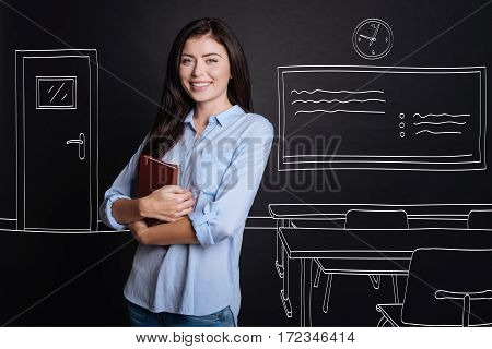 My workign space. heerful diligent professional woman holding notebook and expressing gladness while standing in the classroom