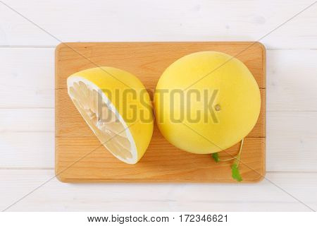 fresh ripe pomelo on wooden cutting board