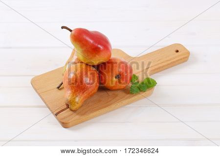 ripe red pears on wooden cutting board