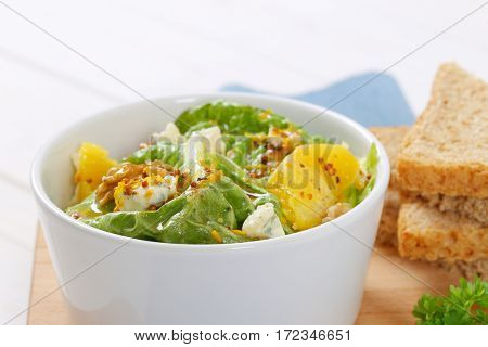 bowl of chinese cabbage salad with orange, walnuts,cheese and toast bread - close up