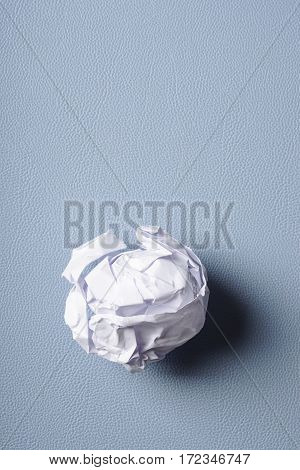 crumpled-up ball of paper on blue desk pad with copy space