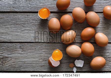 Fresh chicken brown and white home eggs with cracked eggshell and yolk on rustic wood table. Top view with copy space. Rural still life, natural healthy food and organic farming concept.