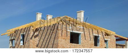 Roofing Construction. Wooden Roof Frame White Chimneys and Yellow Brick House Construction