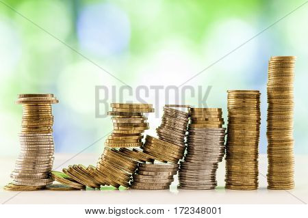 Growing Coins Stacks With Green And Blue Sparkling Bokeh Background. Financial Growth, Saving Money,