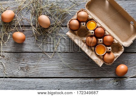 Fresh chicken eggs background. Brown and white eggs in craft carton pack on hay at rustic wood table with copy space. Top view. Natural healthy food and organic farming concept.