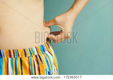 Close up woman hand pinch her belly. Slim woman with copy space. Vintage