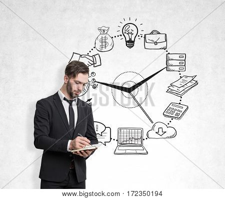 Portrait of a bearded businessman standing with his notebook and pen near a concrete wall with business icons drawn on the face of a clock.