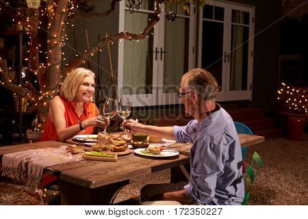 Mature Couple Enjoying Outdoor Meal In Backyard