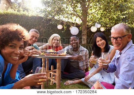 Portrait Of Mature Friends Enjoying Drinks In Backyard