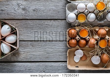 Fresh chicken eggs background. White and brown eggs in craft carton pack on hay at rustic wood table with copy space. Top view. Natural healthy food and organic farming concept.