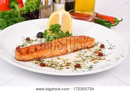 Salmon Steak With Cranberry Sauce Garnished With Dill, Olives And Parsley On A White Plate On A Back