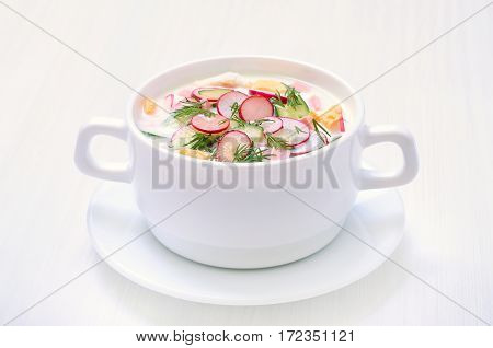 Yoghurt soup with radish cucumber and dill on white table
