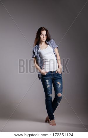 Full length portrait of an attractive girl in casual jeans clothes possing at studio