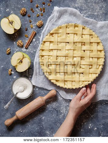 Apple pie tart homemade traditional autumn sweet pastry baked food cooking recipe with ingridients, rolling pin, egg yolk, sugar flat lay on blue vintage background, top view