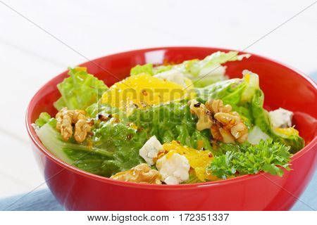 bowl of chinese cabbage salad with orange, walnuts and cheese - close up