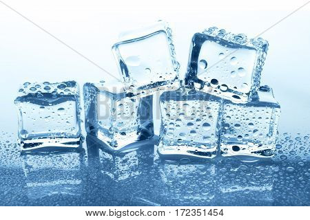 Transparent ice cubes group with reflection on white background. Closeup of cold crystal block on blue glass with water drops