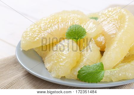 plate of peeled and sliced pomelo - close up