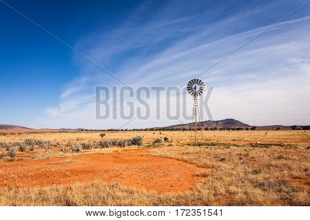 A windmill in a field in the South Australian outback. This windmill stands upon red dirt in the outback between the Flinders Ranges National Park and the state capital, Adelaide.
