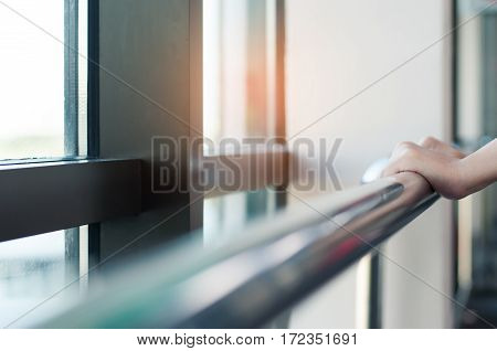 Close up of woman hands holding stainless rail in a room.