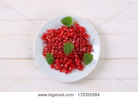 plate of pomegranate seeds on white background