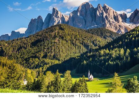 The symbol of the valley Val di Funes - church of Santa Maddalena. Rocky peaks and forested mountains surrounded by green Alpine meadows. Sunny day in  Dolomites