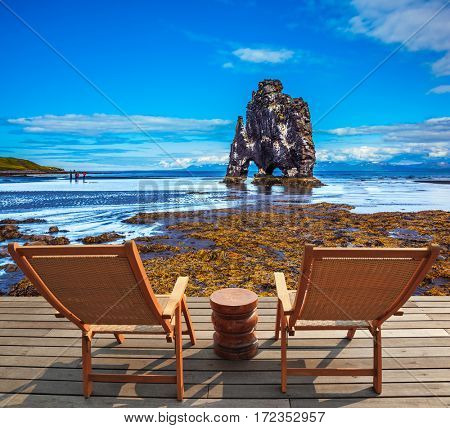 Concept of extreme northern tourism. Magic Rock Hvitsercur on coast of Iceland. Two wooden deck chairs are on the beach