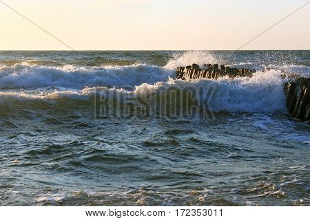The waves of the Baltic Sea breaking on the old wooden german breakwater.