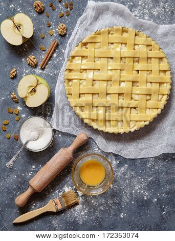 Apple pie tart raw traditional sweet pastry baked food recipe with ingridients, rolling pin, egg yolk, sugar flat lay on blue vintage background, top view
