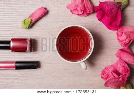 Red flowers and red tea in a white mug isolated on a white background. Space for text and design. Female nail polish and lip gloss. Natural cosmetic. Personal care
