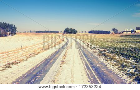 Empty Countryside Road Across Farmland in Winter