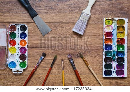 Artistic squirrel brushes tubes of oil paints and watercolors on a wooden background.The palette of twenty-four colors .Used tools for artists and schoolchildren. Tools for art. Set of artistic tools
