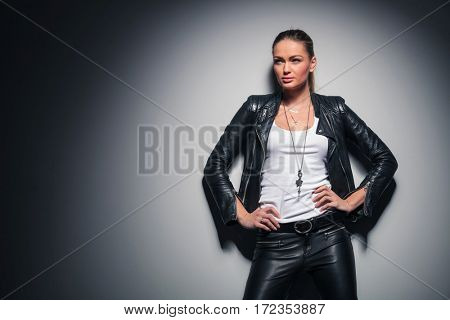 relaxed blonde woman in leather jacket looks away to a side while standing with hands on waist