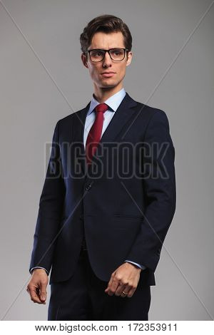 young man in suit and tie wearing glasses looks to side on grey background