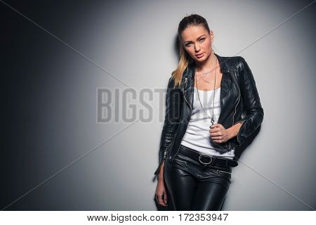 sexy blonde woman in leather clothes posing against grey studio wall