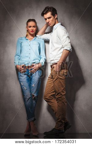 casual man leaning elbow on his girlfriend, full body picture in studio