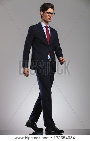 young business man wearing glasses is walking and looks away from the camera, side view pictue in studio