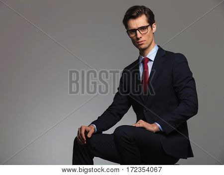 young seated businessman looks at the camera , studio picture with copyspace