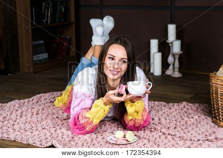 Young brunette woman laying on the floorholding macarons biscuit and a cup of tea