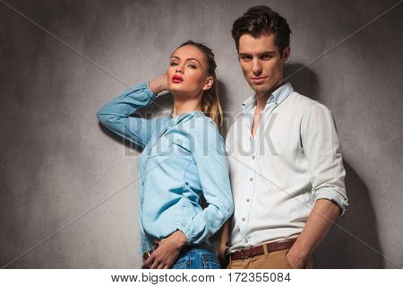 young casual woman with her back at his boyfriend posing together in studio
