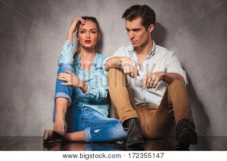 young casual man looks away while sitting near girlfriend in studio