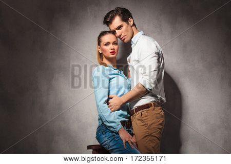 young casual seated woman is embraced by her boyfriend, studio picture