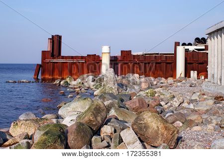 Stones breakwater and rusty iron wall on the Baltic Sea coast.
