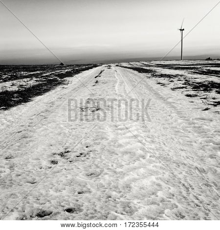 Wintry Field in Snow and Single Wind Turbine Black and White