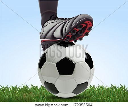Soccer ball with football player feet on green grass