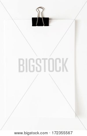 Blank empty sheet of paper attached with clip isolated on white background. Copy space, vertical orientation