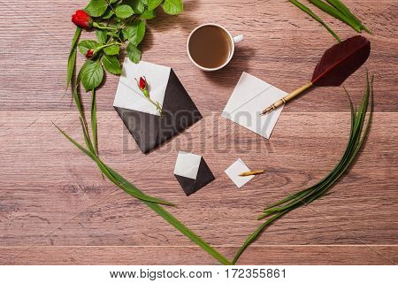 Fountain pen white sheet of paper open envelope a cup of black coffee frame made of grass and roses on a wooden table. Workplace. Write a letter greeting card. Wedding invitation. Flat lay art