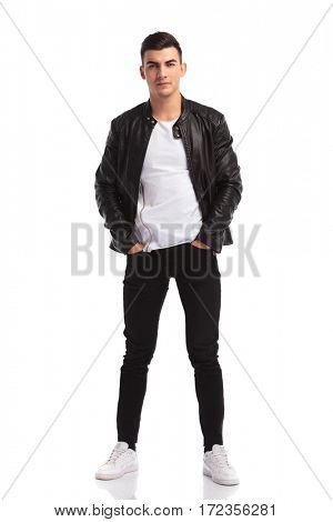 relaxed young man in leather jacket standing with hands in pockets and looks at the camera