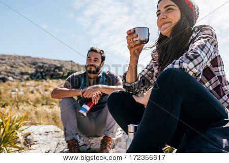 Young woman drinking coffee and resting with friend during hike. Two young friends taking a break during hike.