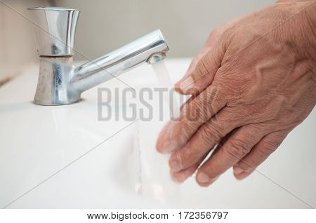 Close up hands Washing and cleaning of hands under running water Old people hands.
