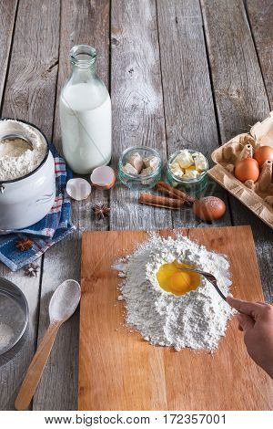 Baking concept. Flour, milk, butter, yeast, spices and eggs carton on rustic wooden table, cooking ingredients. Unrecognizable woman's hands pov view stir dough. Female chef baker